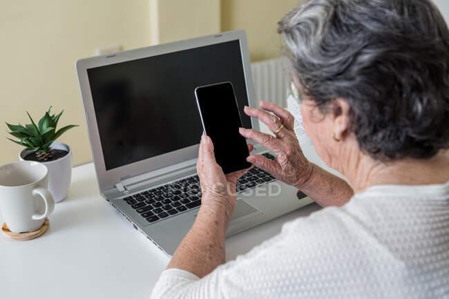 Вид сбоку сосредоточенной пожилой женщины в белой повседневной одежде, сидящей в удобном кресле за столом и использующей смартфон, работая дома на ноутбуке — стоковое фото
