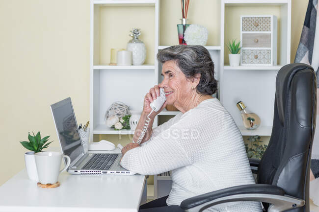Side view of focused elderly woman in white casual clothes sitting in comfortable armchair at table and using phone while working on laptop at home — Stock Photo