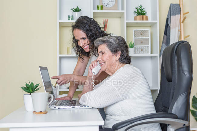Side view of cheerful senior and mature women in casual clothes discussing details of project while working on laptop and talking on telephone at home — Stock Photo