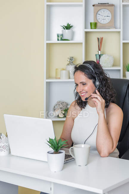 Smiling woman in white blouse sitting at table with cup of hot beverage and using headset while working on laptop at home — Stock Photo