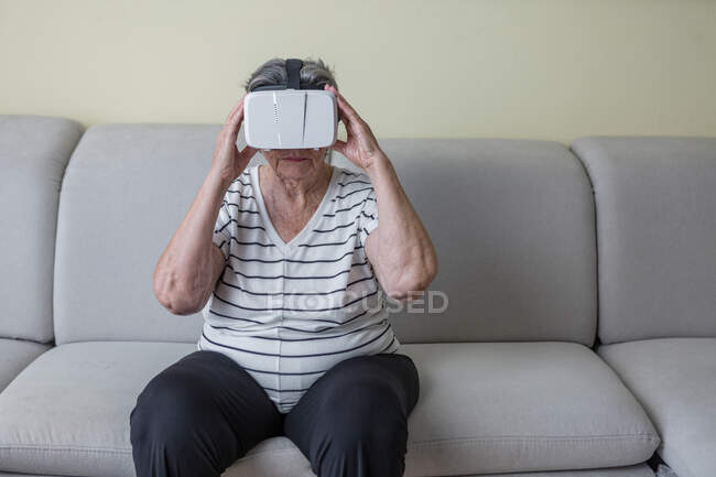 Amazed senior woman in casual clothes wearing goggles of virtual reality exploring another world holding hands up while standing in living room at home — Stock Photo