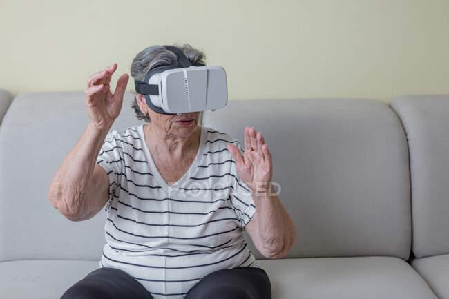 Удивительная пожилая женщина в повседневной одежде в очках виртуальной реальности исследует другой мир, держась за руки, стоя дома в гостиной — стоковое фото