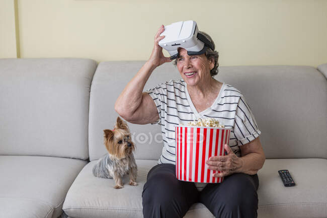Positive elderly lady in casual clothes watching movie in goggles of virtual reality while having basket of popcorn on comfortable sofa with little dog at home — Stock Photo