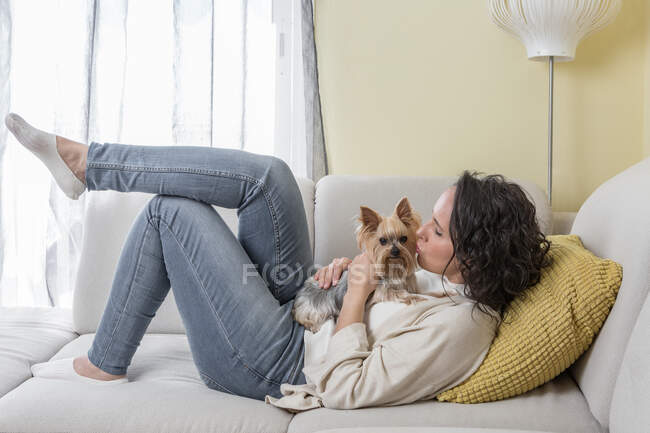 Side view of positive woman in casual clothes kissing Yorkshire terrier dog while resting on comfortable sofa in living room at home — Stock Photo