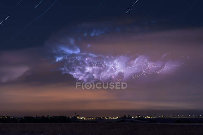 Dramatic dark stormy sky with glowing lightnings over distant city at night — Stock Photo