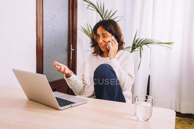 Konzentrierte junge Freiberuflerin in lässiger Kleidung spricht auf dem Smartphone, während sie mit Laptop am Tisch sitzt und zu Hause an einem Projekt arbeitet — Stockfoto