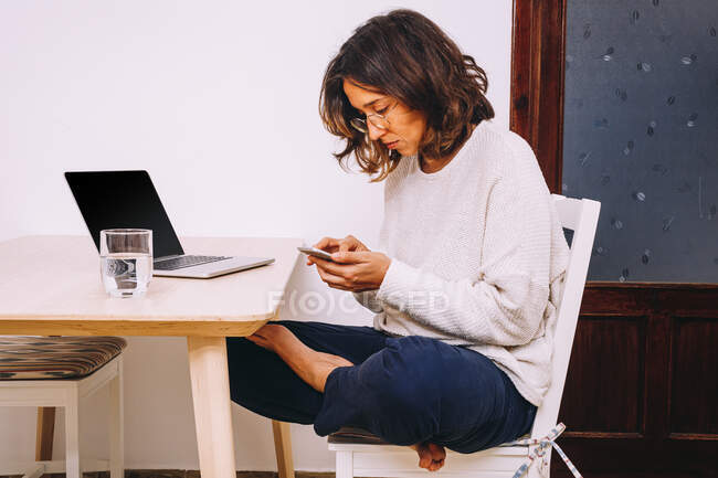 Side view of focused young female freelancer in casual clothes checking messages on smartphone while sitting at table with laptop and working on project at home — Stock Photo