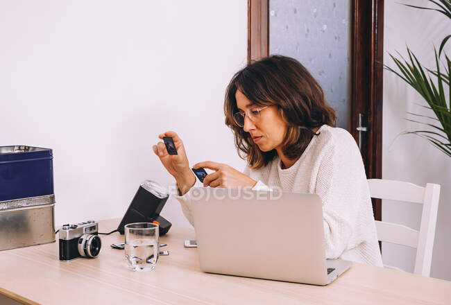 Young female photographer sitting at table with laptop and photo camera with projector and working with old photo slides at home workplace — Stock Photo