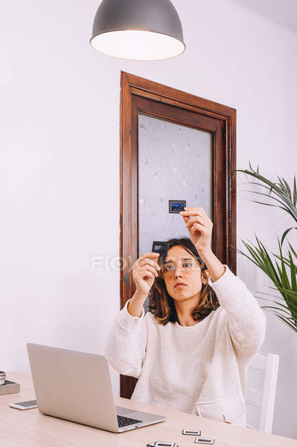 Young female photographer sitting at table with laptop and photo camera with projector and working with old photo slides at home workplace — Stockfoto