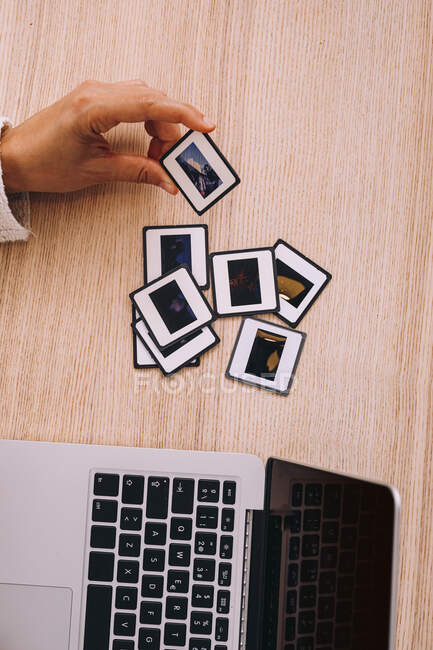 Top view of crop anonymous photographer typing on laptop keyboard while working with old photo slides at table with retro photo camera and modern smartphone — Stockfoto