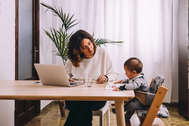 Young female freelancer in casual clothes sitting at table and working on project with laptop while little child sitting nearby with book — Stock Photo