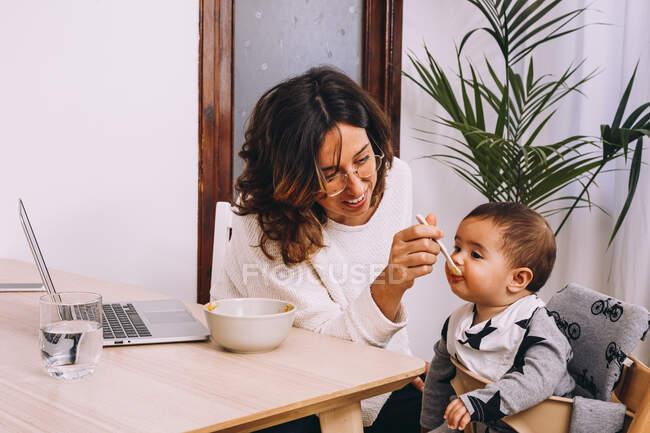 Сучасна молода жінка-віддалений працівник годує маленьку дитину, сидячи за столом з ноутбуком і працюючи над онлайн-проектом. — стокове фото