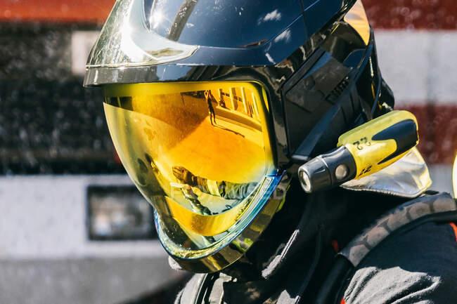 Вид сбоку на неузнаваемого пожарного в защитном шлеме, стоящего на солнечной улице во время тренировки — стоковое фото