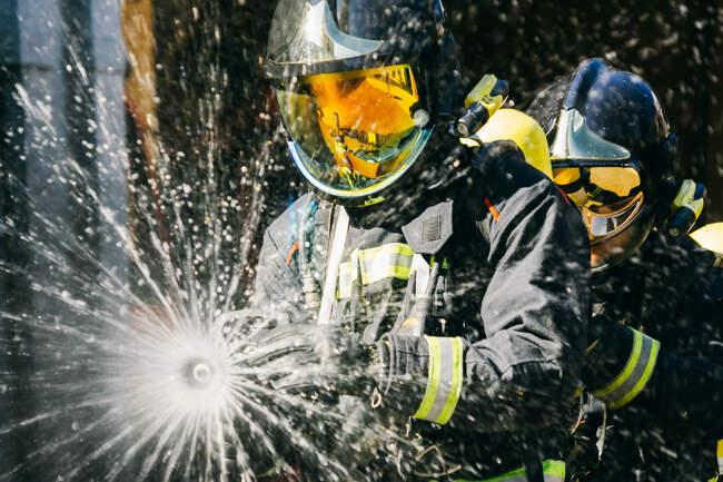 Gesichtslose Feuerwehrleute in Schutzhelmen und Schutzanzügen löschten bei der Übung am sonnigen Tag den Brand mit Wasserschlauch — Stockfoto