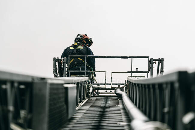 From below of brave fireman standing on aerial platform of fire engine during training on background of gray sky — Foto stock