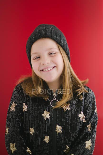 Criança alegre com sorriso de dente em camisa preta quente e gorro de malha olhando para a câmera enquanto estava em pé no fundo vermelho — Fotografia de Stock