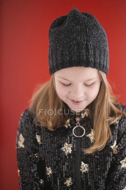 Enfant joyeux avec sourire de dents en jersey noir chaud et bonnet tricoté regardant vers le bas tout en se tenant debout sur fond rouge — Photo de stock