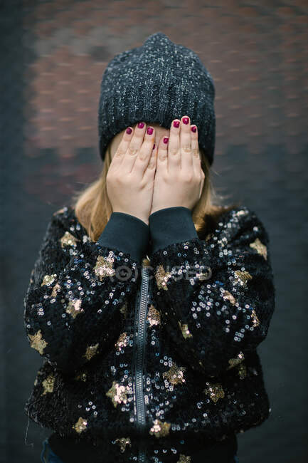 Little anonymous child in knitted cap and warm jacket with manicure on hands covering face while standing outdoors — Stock Photo