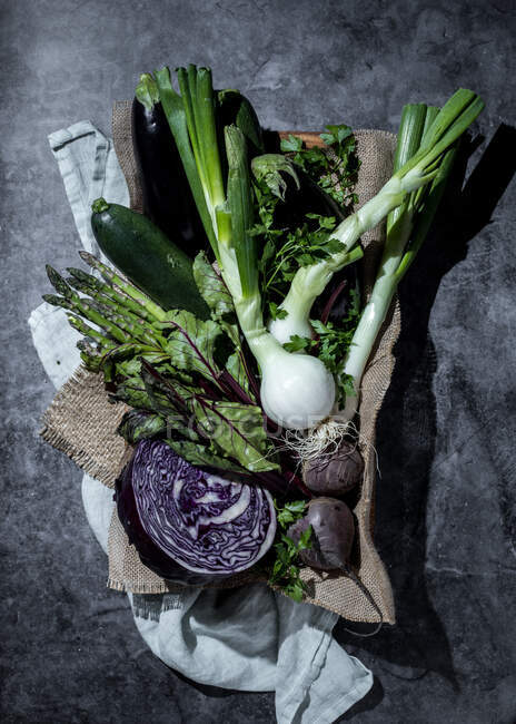 Purple cabbage and beets in composition with other fresh vegetables and herbs on sack fabric — Stock Photo