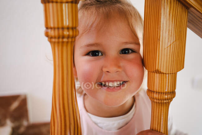 Divertente ragazza carina in camicia bianca ponendo testa tra ringhiere di legno di scale guardando la fotocamera — Foto stock