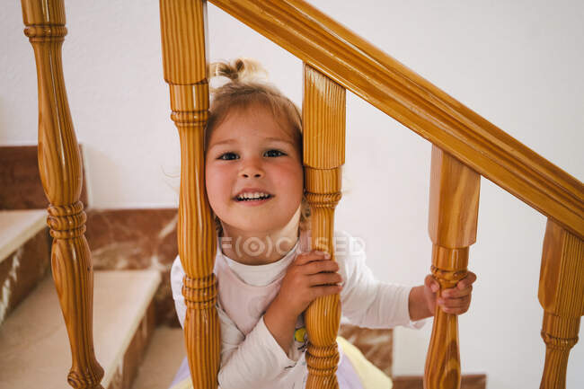 Funny cute girl in white shirt placing head between wooden railings of stairs looking at camera — Stock Photo