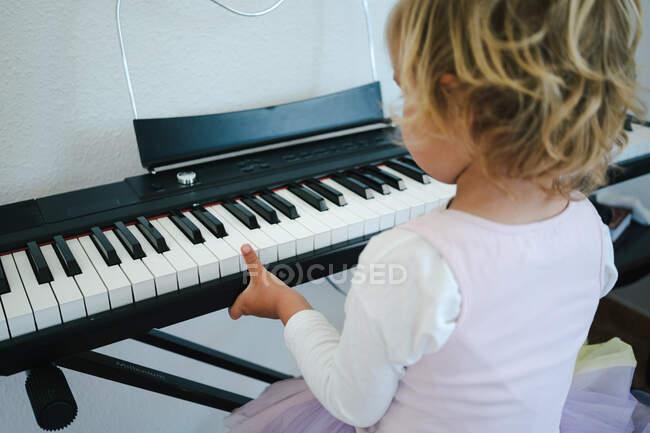 На задньому плані дівчина в пухнастій спідниці сидить за синтезатором і готується до уроків музики, дивлячись на камеру. — стокове фото