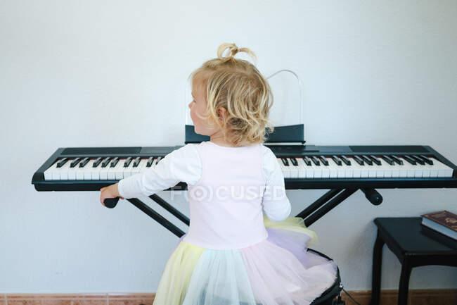 Rückansicht einer Schülerin im flauschigen Rock, die am Synthesizer sitzt und sich auf den Musikunterricht vorbereitet und in die Kamera schaut — Stockfoto