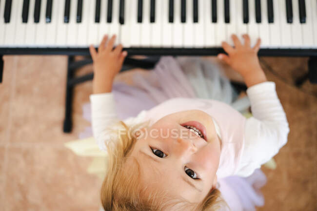 Dall'alto di affascinante bionda bambina ridendo brillantemente alla macchina fotografica durante la riproduzione di sintetizzatore a casa — Foto stock
