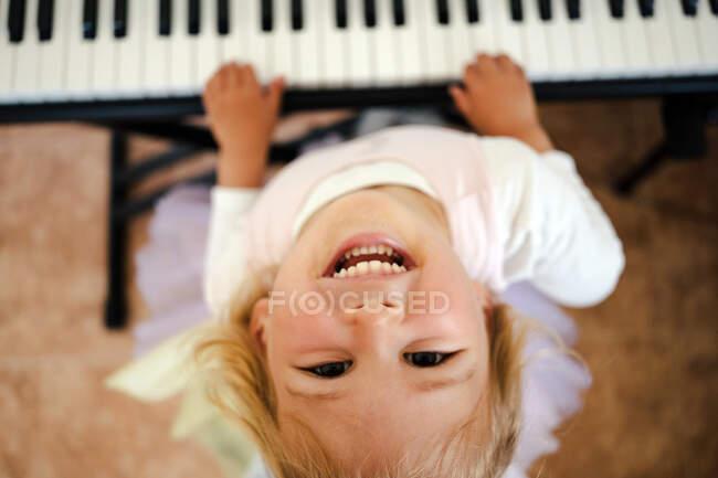 Зверху чарівна блондинка яскраво сміється на камеру, граючи вдома на синтезаторі. — стокове фото
