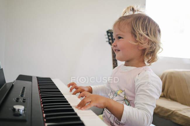 Бічний погляд на школярку в пухнастій спідниці, яка сидить за синтезатором і готується до уроків музики, озираючись. — стокове фото