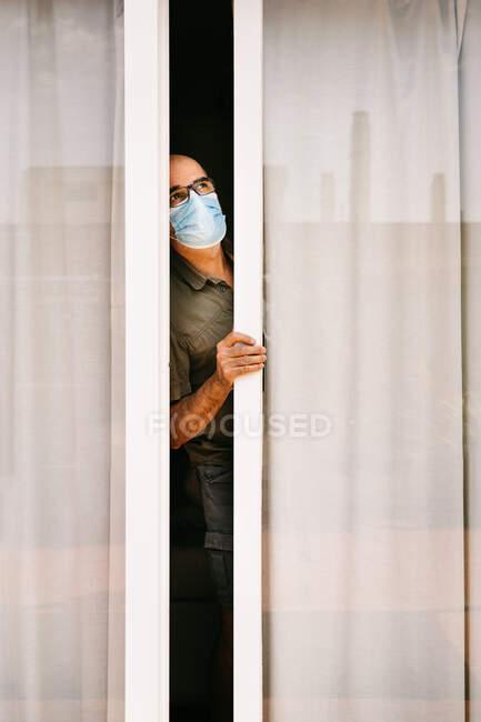 Mulher adulta em máscara médica olhando para a rua com medo durante pandemia de COVID 19 — Fotografia de Stock