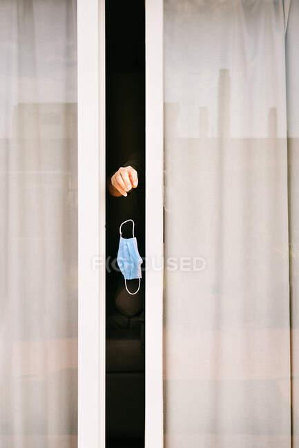 Mão de pessoa anônima saindo da janela ligeiramente aberta segurando máscara protetora permanecendo em quarentena durante o surto de coronavírus — Fotografia de Stock