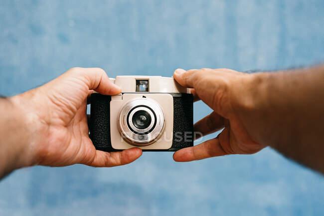 Обрезанные неузнаваемые мужские руки, фотографирующиеся ретро-камерой в светлой студии — стоковое фото
