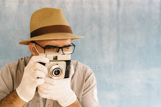 Middle aged man in latex gloves and medical mask taking picture with retro camera in light studio — Stock Photo