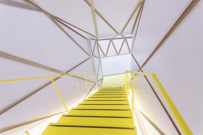 Dall'alto scala illuminata con gradini gialli circondata da elementi geometrici su pareti e soffitto — Foto stock