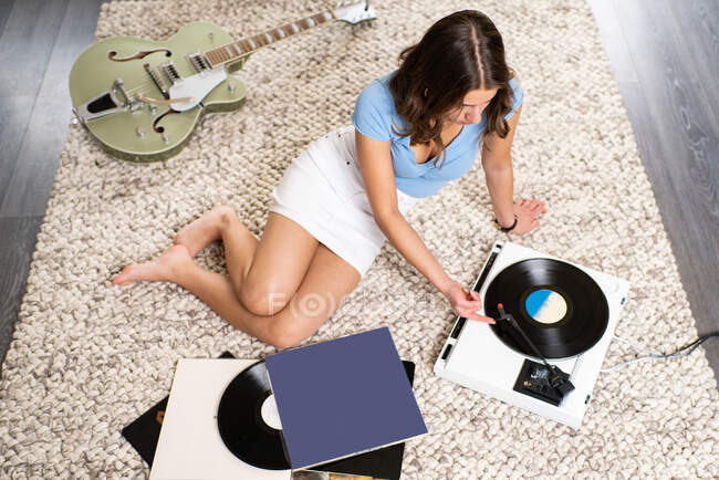 From above of young female meloman in casual outfit sitting on carpet on floor near guitar and listening to music with vinyl disc and record player while resting at home — Stock Photo