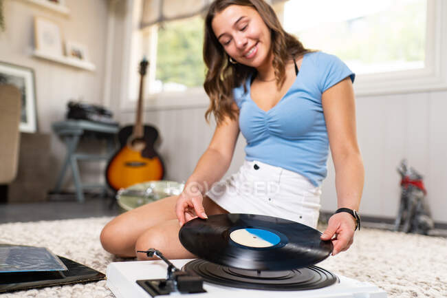 Happy young female meloman in casual outfit sitting on carpet on floor near guitar and listening to music with vinyl disc and record player while resting at home — Stock Photo