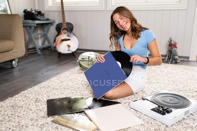 Щаслива молода жінка-меломан у повсякденному одязі сидить на килимі біля гітари і слухає музику з вініловим диском і програвачем під час відпочинку вдома. — стокове фото