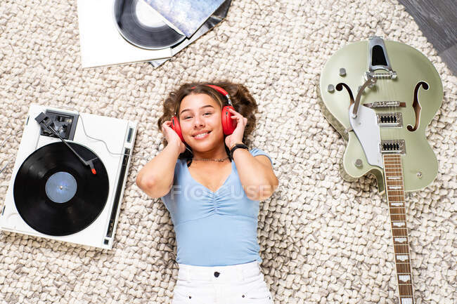 From above of happy young female looking at camera in casual wear lying on floor near guitar and listening to music with headphones and vinyl player while enjoying free time at home — Stock Photo