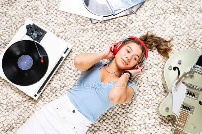 From above of happy young female looking away in casual wear lying on floor near guitar and listening to music with headphones and vinyl player while enjoying free time at home — Stock Photo
