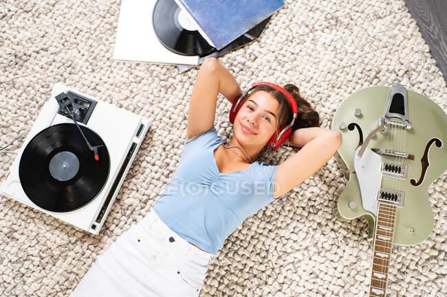 Von oben eine glückliche junge Frau, die in lässiger Kleidung in der Nähe der Gitarre auf dem Boden liegt und mit Kopfhörer und Plattenspieler Musik hört, während sie die Freizeit zu Hause genießt — Stockfoto