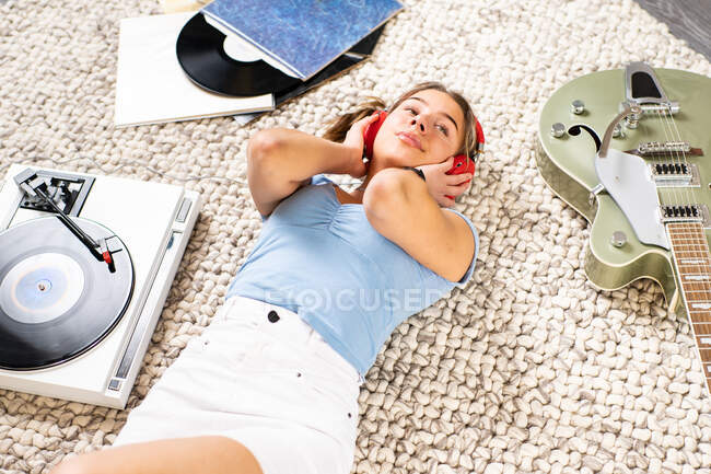 Happy young female looking away in casual wear lying on floor near guitar and listening to music with headphones and vinyl player while enjoying free time at home — Stock Photo