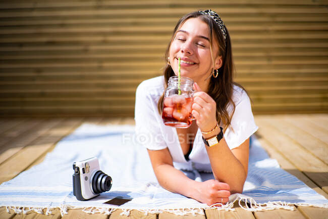 Cheerful young female in casual clothes drinking fresh fruit cocktail and enjoying sunny summer day while lying on terrace near instant photo camera — Stock Photo