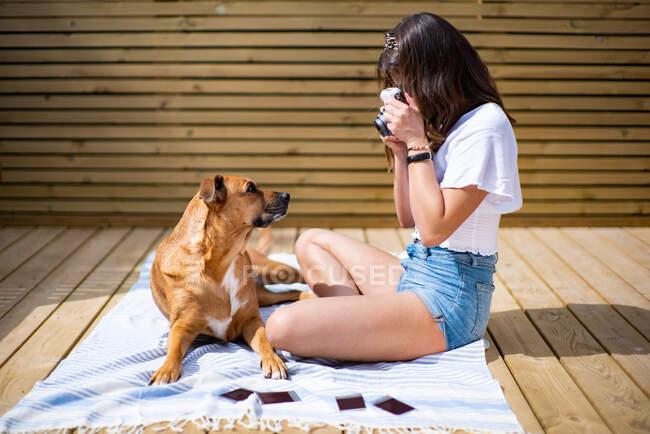 Vista laterale di positivo giovane femmina in camicia casual e pantaloncini jeans scattare foto con fotocamera istantanea di cane carino sdraiato vicino bianco a riposo sulla terrazza soleggiata nella giornata estiva — Foto stock