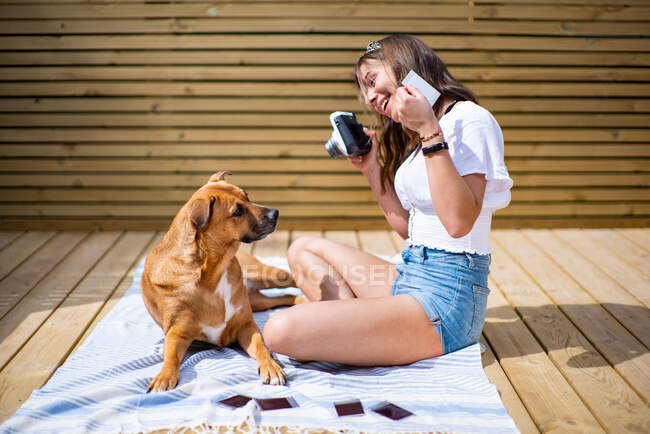 Side view of positive young female in casual shirt and jeans shorts taking pictures with instant camera of cute dog lying nearby white resting on sunny terrace in summer day — Stock Photo