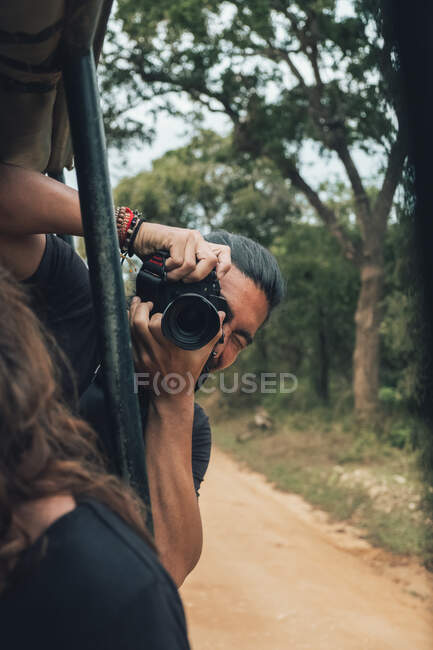 Happy traveling male with professional photo camera taking photos of wildlife during safari — Stock Photo