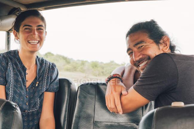 Вид сбоку на многонациональную пару, сидящую за камерой в автомобиле и наслаждающуюся сафари во время летних каникул — стоковое фото