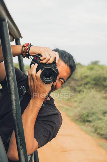 Felice maschio viaggiatore con macchina fotografica professionale scattare foto della fauna selvatica durante safari — Foto stock