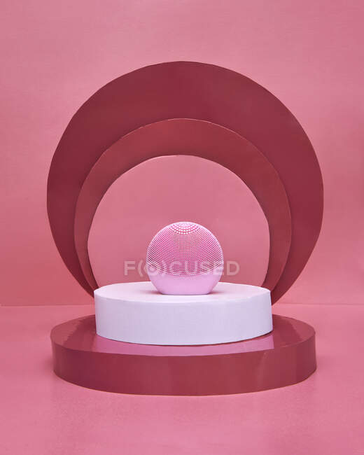 Pink electronic facial cleansing massager placed amidst composition with white and red disks on pink background — Stock Photo