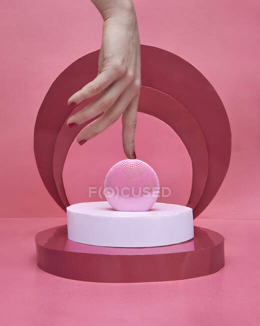 Crop anonymous female with red manicure keeping finger on pink pink electronic facial cleansing massager placed amidst composition with white and red disks on pink background — Stock Photo